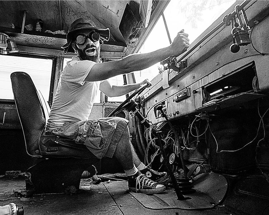 Black and White Fine art portrait of Brad at the wheel of a vintage school bus. Portrait shot on film by Kansas City art photographer Kirk Decker.