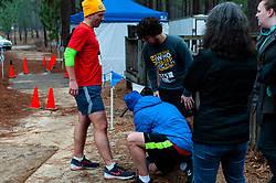 January 19, 2019 - Southern Pines, North Carolina, US - Jan. 19, 2019 - Southern Pines N.C., USA - A relay team swaps out a timing chip during the 10th Annual Weymouth Woods 100km ultra marathon at the Weymouth Woods Nature Preserve. Runners needed to complete 14 laps of the 4.47 mile course for 62.58 miles in under the 20-hour time allotment. (Credit Image: © Timothy L. Hale/ZUMA Wire)