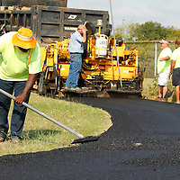 Adam Robison | BUY AT PHOTOS.DJOURNAL.COM<br /> Martin Starks, a Lee County employee, rakes fresh asphalt on the walking track at Saltillo City Park as it was re-paved Monday morning in Saltillo.