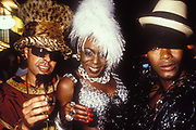 Two black men wearing extravagent headgear and garments and a black women wearing fluffy white hat, thich necklace and white textured dress, Ibiza, 1998.