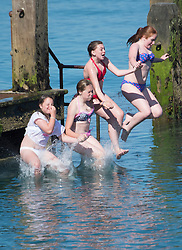 © Licensed to London News Pictures. 25/07/2014. Aberystwyth, UK With temperatures already in the mid 20s centigrade soon after 10am, early morning swimmers have fun jumping off the wooden jetty on the beach at Aberystwyth on the west wales coast UK. Todays peak temperature is forecast to be around 25c, a few degrees cooler than recent days but still above the average for this time of year. Photo credit : Keith Morris/LNP