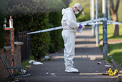 © Licensed to London News Pictures . 07/05/2018. Manchester , UK. Forensic examiners and police conduct a fingertip search and remove evidence in a cordoned off area of Vale Street in Clayton , East Manchester , after responding to the shooting of a teenager , this Bank Holiday Monday afternoon (7th May 2018) . Photo credit : Joel Goodman/LNP