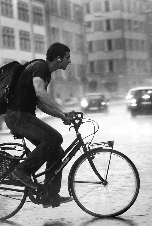 A man on bike in rain in Bologna.