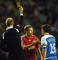 Photo: Paul Greenwood.<br />Wigan Athletic v Liverpool. The Barclays Premiership. 02/12/2006. Referee Mike Reilly issues Craig Bellamy with a yellow card as he protetst his innocence with Wigan's Leighton Baines