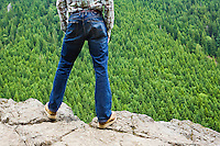 A man standing on a rock ledge looking out over a large forested mountainside.  Washington, USA.