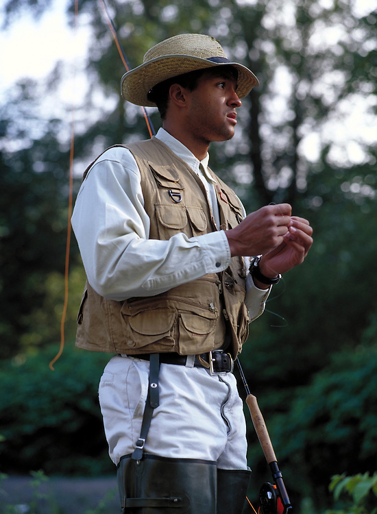 Lifestyle image of young man tying a fly before fishing on the Cedar River in Washington State.