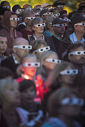© Licensed to London News Pictures . 20/07/2013 . Suffolk , UK . Large crowds wearing 3D glasses watch as Kraftwerk perform their 3D show on the Obelisk Stage . The Latitude music and culture festival in Henham Park , Southwold . Photo credit : Joel Goodman/LNP