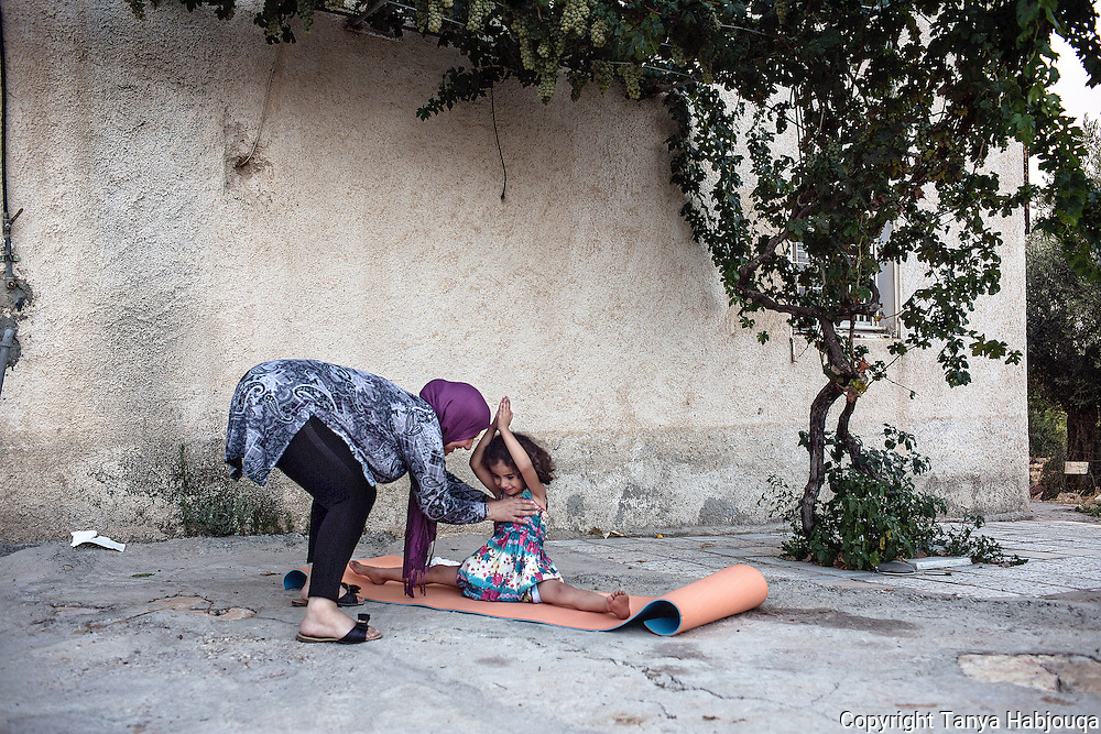 A mother takes moment to teach her daughter yoga before it is time to break fast and eat together during Ramadan. Jaleela Khwaja, a 42 year yoga instructor who has been leading classes Ni&rsquo;lin for a year is on break for Ramadan as fasting during the summer heat is not popular. The classes will resume after Eid.<br /> <br /> However, she and her daughters like to practice yoga before iftar (the breaking of their fast at sunset) in their back yard. <br /> <br /> Here, she and her five year old, Saja, practice yoga together.