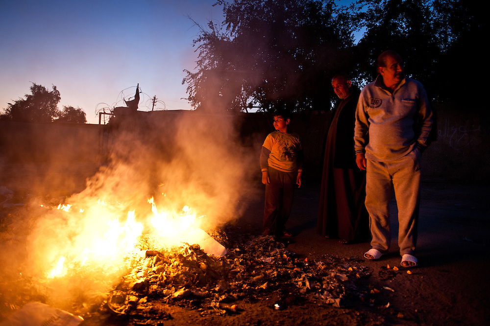 A family burns trash in a once prosperous Baghdad neighborhood. There has been no virtually no organized trash collection in Baghdad since Saddam Hussein's regime fell.