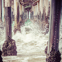 Under the pier vintage California picture with waves crashing into wooden pier support posts. Balboa Pier is on Balboa Peninsula in Newport Beach, Orange County, California. Photo has a vintage 1950s tone.