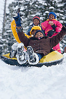 Young kids riding snowtube at Kirkwood ski resort near Lake Tahoe, CA.