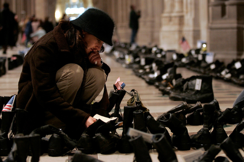 "Washington, Jan. 17, 2005 - Ilyssa Parker takes a closer look at a pair of soldier's boots that are a part of the ""Eyes Wide Open"" display during its stop at the Washington National Cathederal on Jan. 17, 2005.  There are one pair of boots for each American soldier killed in Iraq, today's total was 1365.  (Jay Westcott/Journal)"