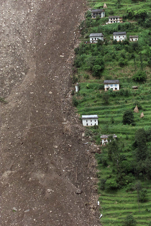 Nepalese homes stand in a lush green valley of  rice fields spared by the raging lanslide waters next to the ravaged area of the natural disaster that is the single most deadly monsoon caused incident this year in South Asia, in the Nepalese village of Thapru Friday Aug. 23, 2002. 41 people remain missing and are presumed dead, 13 bodies have been rescued,  and only 28 villagers survived Wednesday's himalayan disaster that destroyed most of the foothill village.