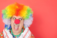 Senior male clown sticking out tongue while looking away over red background