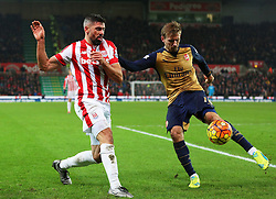 Arsenal's Nacho Monreal clears the ball under pressure from Jonathan Walters of Stoke City  - Mandatory byline: Matt McNulty/JMP - 17/01/2016 - FOOTBALL - Britannia Stadium - Stoke, England - Stoke City v Arsenal - Barclays Premier League