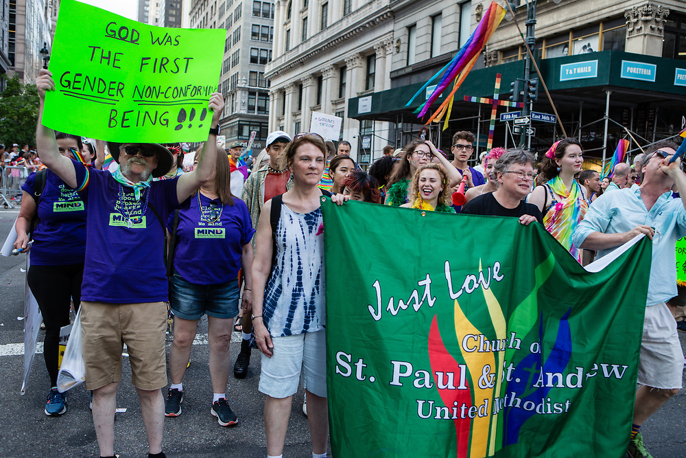 "New York, NY - 25 June 2017. New York City Heritage of Pride March filled Fifth Avenue for hours with groups from the LGBT community and it's supporters. Marchers fro the Church of St. Paul and St Andrew, one of whom carries a sign that reads ""God was the first gender non-conforming being!!!"""