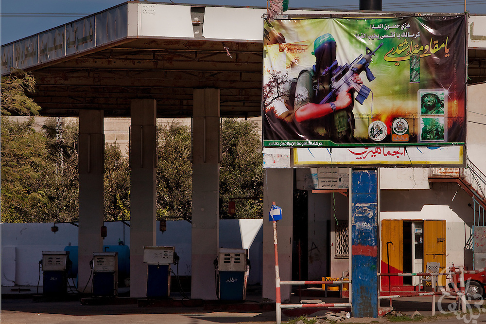A billboard celebrating the armed wing of HAMAS stands over a Palestinian gas station in Khan Yunis December 19, 2009. Although Israel allows some fuel to pass through to Gaza, HAMAS also smuggles much larger quantities through tunnels from Egypt effectively keeping prices low and helping retain popular support for their government. Fuel smuggled from Egypt only costs on average one tenth the amount as the Israeli imported fuel.