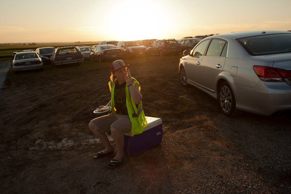 Juliana Logan, 16, of Davenport takes a break for dinner while keeping an eye on the traffic at Camp Euforia north of Lone Tree on Friday, July 17, 2015. Following a thunderstorm on Thursday night, the parking area turned muddy and impassable, prompting fest organizers to bring a load of gravel to mitigate the greasy conditions.