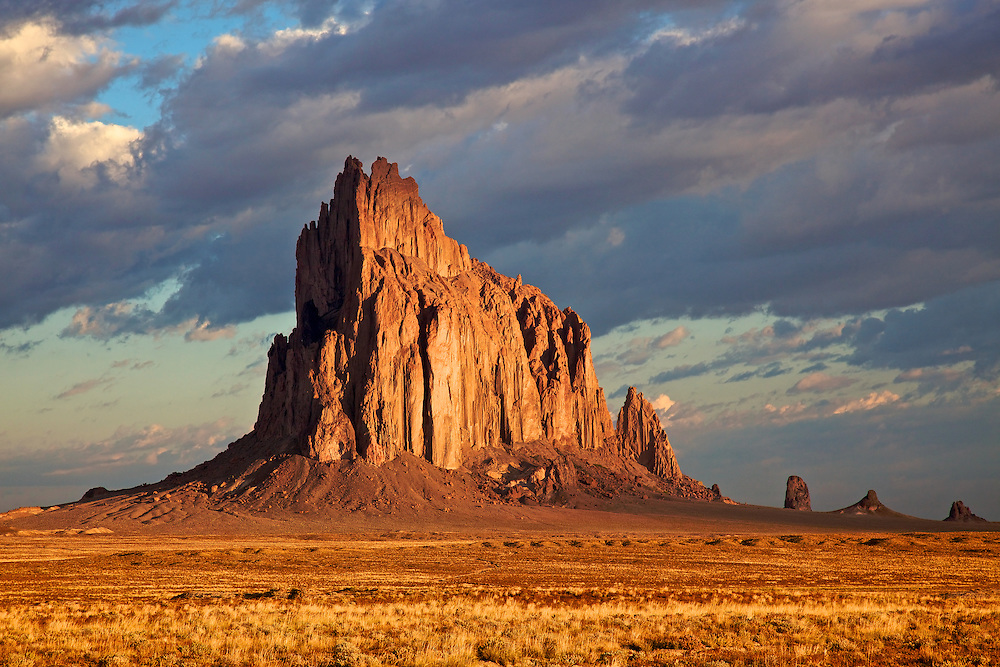 "Shiprock (Navajo: Tsé Bit'a'í, ""rock with wings"" or ""winged rock"") is a rock formation rising nearly 1,583 feet  above the high-desert plain on the Navajo Nation in San Juan County, New Mexico."