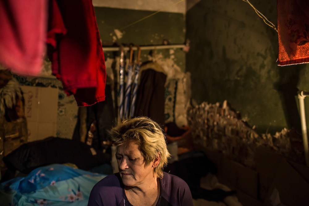 DONETSK, UKRAINE - JANUARY 29, 2015: Lyubov Pavlova, 55, sits in her room in an underground bomb shelter in the Petrovskyi district of Donetsk, Ukraine. The neighborhood has been shelled heavily in the past few days, forcing many people back to the shelters they first fled to in the summer. CREDIT: Brendan Hoffman for The New York Times