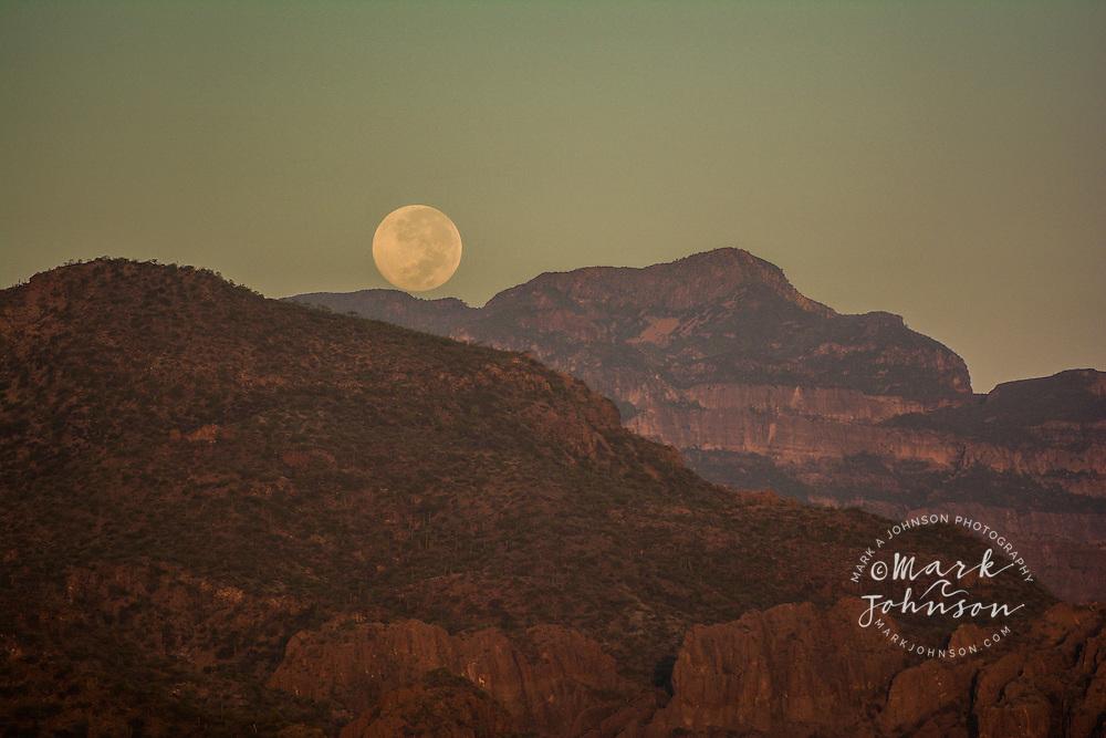 Full moon setting behind the Sierra de los Gigante mountain range, Baja California Sur, Mexico
