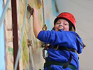 Autumn Herndon, 13, of Marion, looks down while working her way up the climbing wall during the Retreat & Refresh Stroke Camp at Camp Courageous in Monticello on Saturday, April 20, 2013.