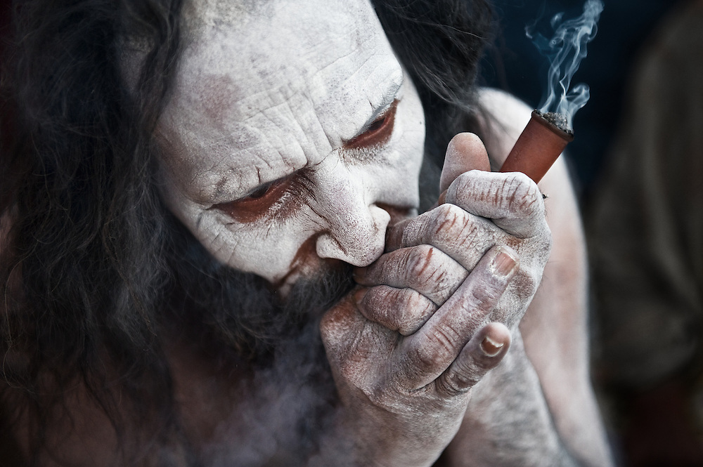 An Ash smeared Naga Sadhu smoking pot during the Kumbh Mela, 2010.<br /> <br /> The consumption of bhang is also considered to be a part of the rituals performed by the Naga Babas. The sadhus hold the view that doing so will lead them to nirvana, meaning the final emancipation of the soul.<br /> <br /> Naga Sadhus belong to the Shaiva sect, they have matted locks of hair and their bodies are covered in ashes like Lord Shiva.<br /> <br /> Kumbh Mela, 2010, Haridwar, Uttarakhand.