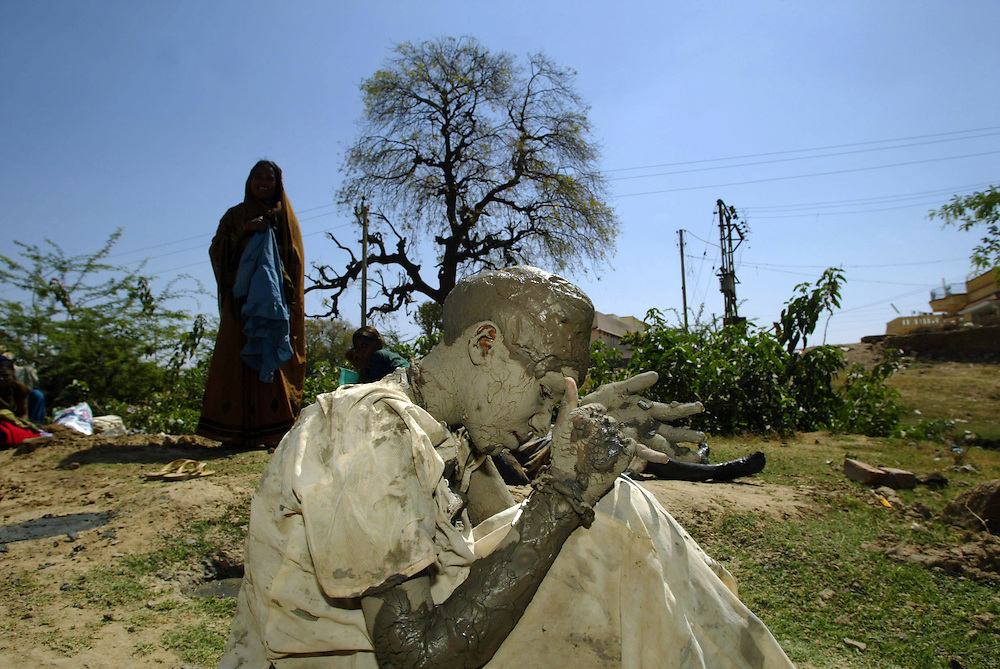 A woman shackled with chains and locks covers herself in mud as part of a purifying ritual  to unburden herself outside of the  Mira Datar Shrine in the town of Unava, Gujarat Thursday March 4, 2004. Over six centuries the Suffi Muslim Mira Datar shrine has claimed its fame as a sanctuary for healing mental ilness, particularly for women, where they are free to express themselves  in a society that otherwise regulates women's behaviour very strickly. In this atmosphere of acceptance these women often reveal through their healing trances a lifetime of duress linked to any range of  issues such domestic violence, pressures to provide dowry or a male child among them.