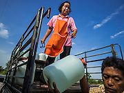 14 JULY 2015 - THAILAND: A woman unloads jugs of drinking water in a village in Pathum Thani province. The drought that has crippled agriculture in central Thailand is now impacting residential areas near Bangkok. The Thai government is reporting that more than 250,000 homes in the provinces surrounding Bangkok have had their domestic water cut because the canals that supply water to local treatment plants were too low to feed the plants. Local government agencies and the Thai army are trucking water to impacted communities and homes. Roads in the area have started collapsing because of subsidence caused by the retreating waters. Central Thailand is contending with drought. By one estimate, about 80 percent of Thailand's agricultural land is in drought like conditions and farmers have been told to stop planting new acreage of rice, the area's principal cash crop.       PHOTO BY JACK KURTZ