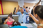 """25 AUGUST 2012 - PHOENIX, AZ: A volunteer holds up the paperwork immigrants need to complete to apply for deferred action status at a workshop in Phoenix. Hundreds of people lined up at Central High School in Phoenix to complete their paperwork to apply for """"Deferred Action"""" status under the Deferred Action for Childhood Arrivals (DACA) program announced by President Obama in June. Volunteers and lawyers specialized in immigration law helped the immigrants complete the required paperwork. Under the program, the children of undocumented immigrants brought to the US before they turned 16 years old would not be subject to deportation if they meet a predetermined set of conditions.     PHOTO BY JACK KURTZ"""