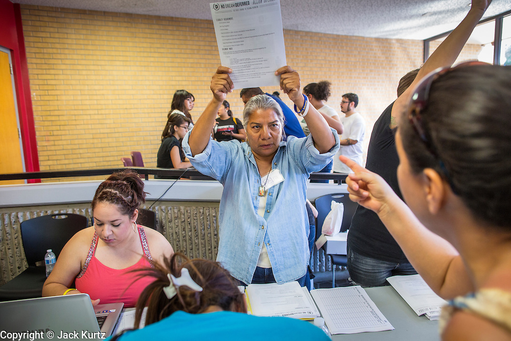 "25 AUGUST 2012 - PHOENIX, AZ: A volunteer holds up the paperwork immigrants need to complete to apply for deferred action status at a workshop in Phoenix. Hundreds of people lined up at Central High School in Phoenix to complete their paperwork to apply for ""Deferred Action"" status under the Deferred Action for Childhood Arrivals (DACA) program announced by President Obama in June. Volunteers and lawyers specialized in immigration law helped the immigrants complete the required paperwork. Under the program, the children of undocumented immigrants brought to the US before they turned 16 years old would not be subject to deportation if they meet a predetermined set of conditions.     PHOTO BY JACK KURTZ"