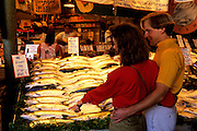 Image of a couple buying fish at Pike Place Market, Seattle, Washington, Pacific Northwest, model released