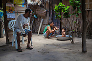 Aurideia Brito feeds her nephew while Aldemir watches them in their house in the Queimada dos Britos.   In this small oasis around 60 people live in. In the oasis everybody is a relative, cousins intermarrying frequently as a normal course. The legend says that the founder Manuel Brito, when running away from home due to a drought that was scorching his homeland, he ended up settling down in the only non-sandy portion of the Lençois.