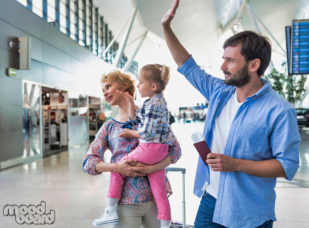 Man waving and holding his passport boarding pass while his wife is carrying their daughter