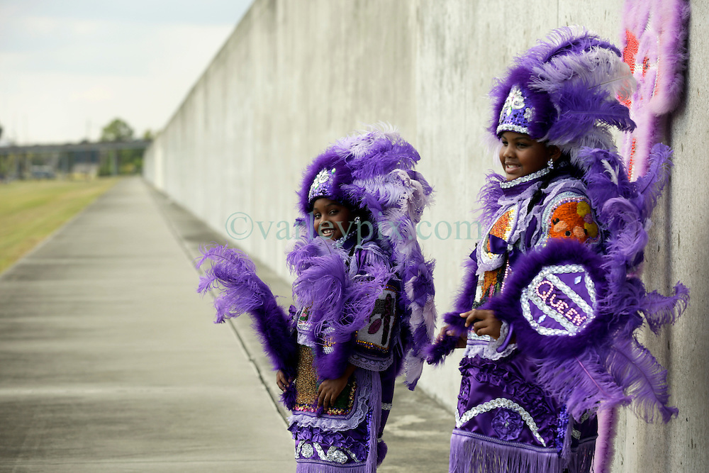29 August 2015. Lower 9th Ward, New Orleans, Louisiana.<br /> Hurricane Katrina 10th anniversary memorial.<br /> L/R; Tia (7 yrs) and Takiera (9 yrs) Augustin of the 9 Red Hawk Mardi Gras Indians at the levee wall which gave way a decade earlier. <br /> Photo credit&copy;; Charlie Varley/varleypix.com.