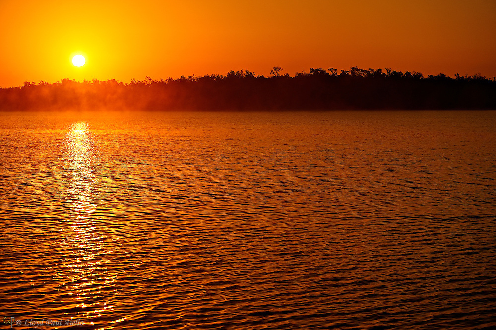 The waters of Plate Creek Bay reflect an orange early morning sky as sea mist is lit by the rising sun in the Florida Everglades