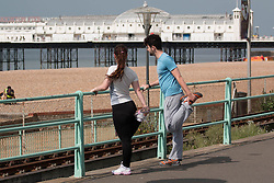 © Licensed to London News Pictures. 31/05/2014. Brighton, UK. A couple warming up for their morning run on the seafront. The weekend is expected to reach temperatures of 20C down the South Coast according to the MET office. Photo credit : Hugo Michiels/LNP