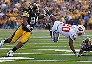 October 23 2010: Wisconsin Badgers running back James White (20) is tripped up by Iowa Hawkeyes defensive end Adrian Clayborn (94) and Iowa Hawkeyes cornerback Micah Hyde (18) after a catch during the first half of the NCAA football game between the Wisconsin Badgers and the Iowa Hawkeyes at Kinnick Stadium in Iowa City, Iowa on Saturday October 23, 2010. Wisconsin defeated Iowa 31-30.