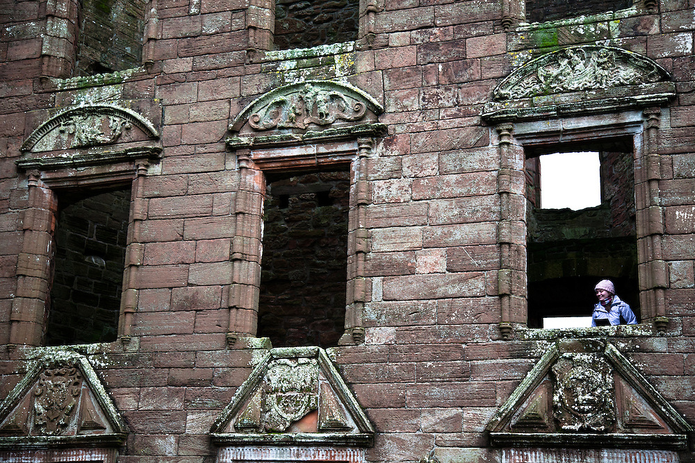 A girl looks though a 1st floor window of Caerlaverock Castle.Caerlaverock Castle is a moated triangular castle, built in the 13th century, in the Caerlaverock National Nature Reserve area at the Solway Firth, south of Dumfries in the southwest of Scotland. In the Middle Ages it was owned by the Maxwell family. Today, the castle is in the care of Historic Scotland and is a tourist attraction and popular wedding venue. It is protected as a scheduled monument, and as a category A listed building.