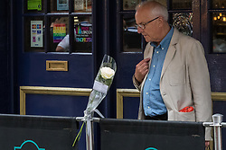 "Compton Street, Soho, London, June 13th 2016. A pair of white roses, a solemn memorial to the 50 people killed at gay club Pulse in Orlando on 12 June, is attached to the balustrade outside The Admiral Duncan, a LGBT-friendly bar that knows too well the price of homophobia, bombed by Neo-Nazi David Copeland on 30 April 1999, killing three people and wounding 70. The message on the card reads, ""Compton Street, Soho, London, June 13th 2016. A pair of white roses, a solemn memorial to the 50 people killed at gay club Pulse in Orlando on 12 June, is attached to the balustrade outside The Admiral Duncan, a LGBT-friendly bar that knows too well the price of homophobia, bombed by Neo-Nazi David Copeland on 30 April 1999, killing three people and wounding 70. The message on the card reads, ""To Orlando, LOVE IS LOVE! Soho stands with you."" and is signed ""James and Talia"". PICTURED: A man crosses himself as he looks at the roses."