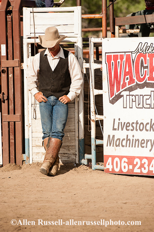 Ty Linger, chute crew, relaxes between bronc riders, Miles City Bucking Horse Sale, Montana.