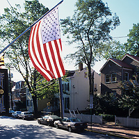 USA, Maryland, Annapolis, American flag flies in front of B&B in downtown on autumn morning