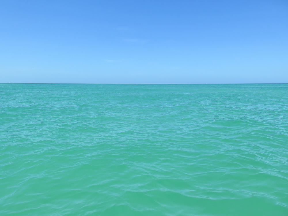 Blue sky and green seas in Florida on a sunny cloud free summer day