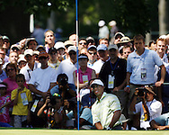 Tiger Woods of the US chips in front of the gallery around the sixth hole during the first day of the US Open Golf Championship at Winged Foot Golf Club in Mamaroneck, New York Thursday, 15 June 2006.