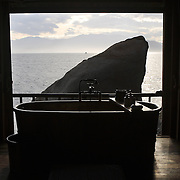 A Water Villa's private bathroom overlooks the ocean past a large boulder at the Evason Hideaway in Nha Trang, Vietnam.
