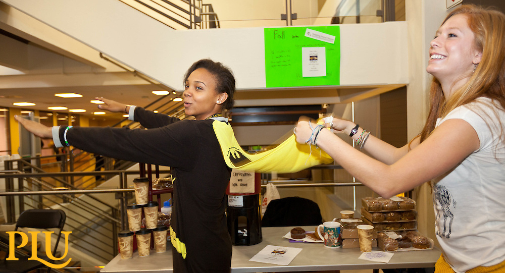"Lexi Johnson '18, AKA ""bat woman"" has a bit of help filling her cape with air from Genny Boots '18, during the while trying to attract customers to their business as part of a business venture project  at PLU on Thursday, Oct. 30, 2014. (PLU Photo/John Froschauer)"