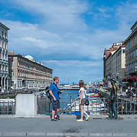 Tourists take pictures at James Joyce's statue on the literary trail on the Gran Canale in Trieste, Italy