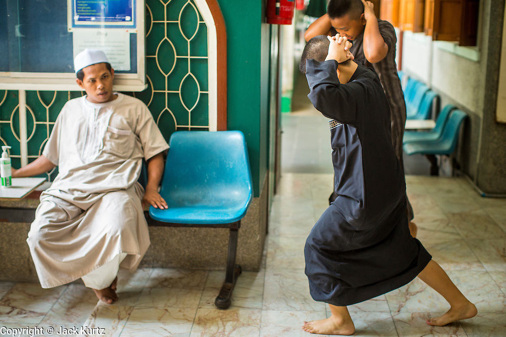 """11 JANUARY 2013 - BANGKOK, THAILAND: Boys do exercises after being caught misbehaving on their way to Mosque for noon prayers in the Ban Krua neighborhood in Bangkok. The Ban Krua neighborhood of Bangkok is the oldest Muslim community in Bangkok. Ban Krua was originally settled by Cham Muslims from Cambodia and Vietnam who fought on the side of the Thai King Rama I. They were given a royal grant of land east of what was then the Thai capitol at the end of the 18th century in return for their military service. The Cham Muslims were originally weavers and what is known as """"Thai Silk"""" was developed by the people in Ban Krua. Several families in the neighborhood still weave in their homes.                   PHOTO BY JACK KURTZ"""