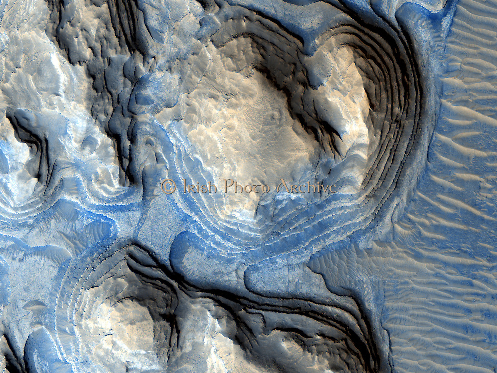 "Geologic layering on Mars. image from the HiRISE high-resolution camera on board the Mars Reconnaissance Orbiter (MRO) shows multiple layers of exposed sedimentary rock on Mars in a region known as Arabia Terra. Referred to as ""cyclic bedding"" by geologists, this pattern of layering is caused by repeated fluctuations in the amount of sediment available to create new rock layers. This is often caused by long-term changes in the climate of a region, or even by wobbles in a planet's rotation which can make certain areas experience long periods of dry climate followed by periods of wetter climate."