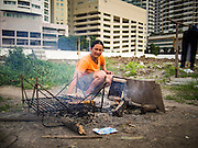 05 SEPTEMBER 2013 - BANGKOK, THAILAND:  A Cambodian woman cooks her dinner after her shift on the construction site of a new high rise apartment / condominium building on Soi 22 Sukhumvit Rd in Bangkok. Other residential high rise buildings ring the site. The workers live in the corrugated metal dorms on the site. Most of the workers at the site are Cambodian immigrants.             PHOTO BY JACK KURTZ